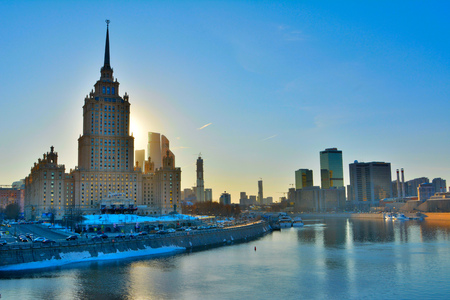 Moscow, Russia - March 24, 2018. Exterior view of Radisson Hotel in Moscow, across Moscow River, at sunset, with surrounding buildings and cars. Editöryel