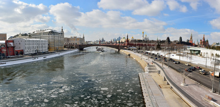 Moscow, Russia - March 17, 2018. View over Moscow River toward Kremlin, from Zaryadye park, with historic buildings, city traffic and cruising vessels.