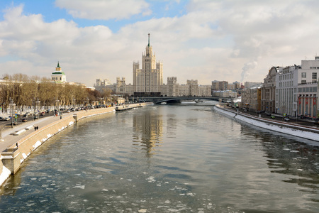 Moscow, Russia – March 17, 2018. View over Moscow River toward Kotelnicheskaya Embankment building, with historic buildings, city traffic and people.