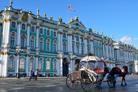 St Petersburg, Russia - March 26, 2018. Exterior view of the Hermitage museum building on Palace Square (Dvortsovaya square)  in St Petersburg, with people and horse-driven carriage. Editorial
