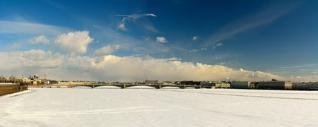 St Petersburg, Russia - March 27, 2018. Panoramic view toward Troitskiy bridge in St Petersburg, with frozen Neva river, architectural residential and commercial buildings and people. Stok Fotoğraf - 114382600