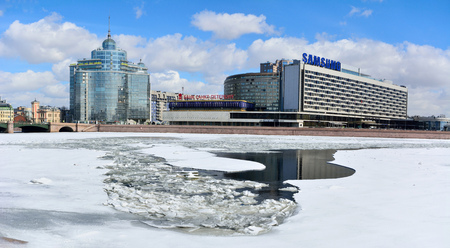 St Petersburg, Russia - March 27, 2018. View of Pirogovskaya embankment of Bolshaya Nevka river in St Petersburg, with commercial and residential buildings, from across frozen river. Stok Fotoğraf - 114382606