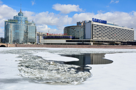 St Petersburg, Russia - March 27, 2018. View of Pirogovskaya embankment of Bolshaya Nevka river in St Petersburg, with commercial and residential buildings, from across frozen river.