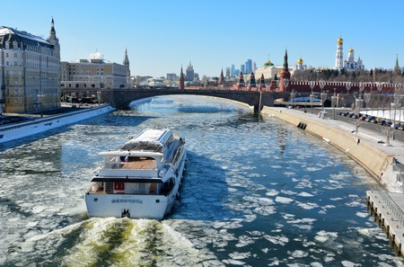 Moscow, Russia - March 18, 2018. View over Moscow River toward Kremlin, from Zaryadye park, with cruising vessel, historic buildings and city traffic. Stok Fotoğraf - 114382620