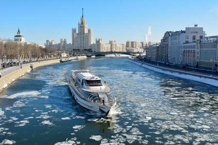 Moscow, Russia - March 18, 2018. View over Moscow River toward Kotelnicheskaya Embankment building, with cruising vessel, historic buildings, city traffic and people.