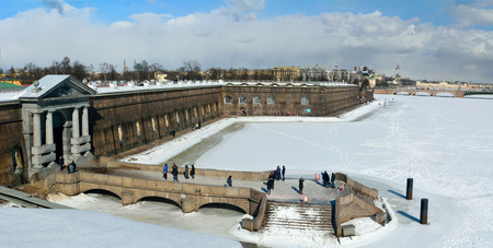 St Petersburg, Russia - March 27, 2018. Exterior view of Peter and Paul Fortress walls and frozen Neva River, toward Trinity Bridge, with people.