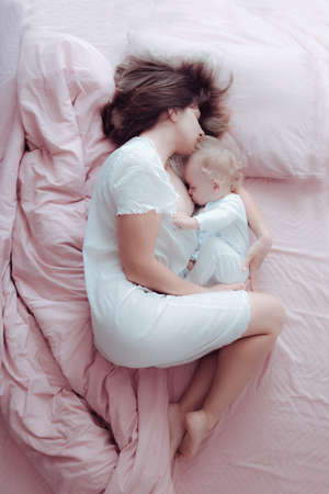 A young mother breastfeeds her baby lying in a pink bed. Hugs his. Sleeping Standard-Bild - 112394854