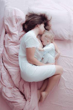 Una joven madre amamanta a su bebé acostado en una cama rosa. Abraza el suyo. Dormido