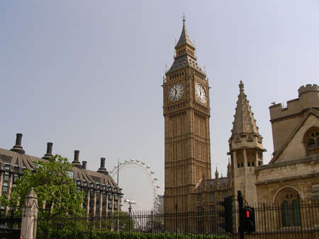 The tower of The Houses of Parliament or Big Ben in London and London Eye in the background photo