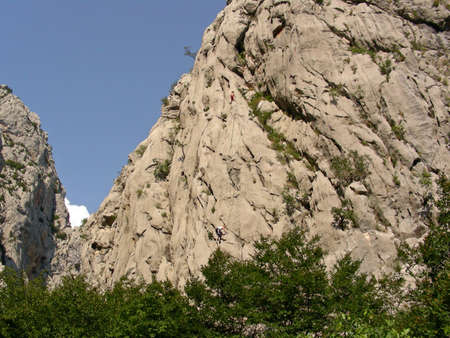paklenica: A massive rock wall in Paklenica National Park with climbers on the way to the top