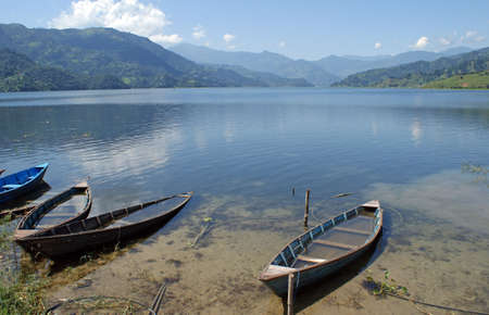 tal: SmaLL wooden boats at the shore of the Phaew Tal lake next to Pokhara in Nepal