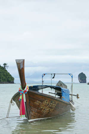 A traditional longtail boat in Thailand seen in the Andaman Sea between limestone rockformations