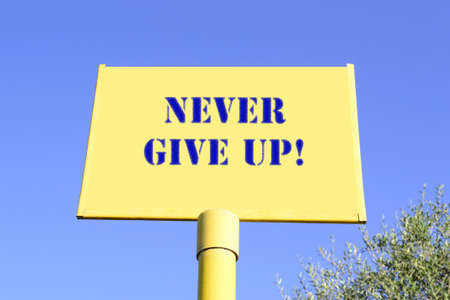 never give up written on a yellow road sign
