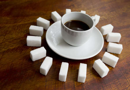 cup of coffee surrounded by several sugar lumps photo