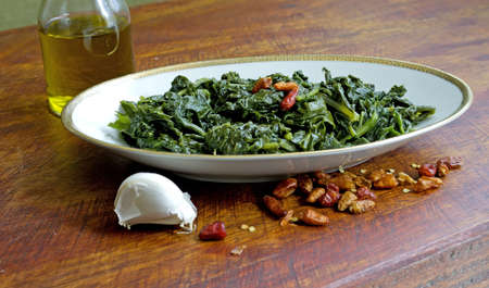 cime di rapa in a plate with garlic, red hot chilli peppers and a cruet