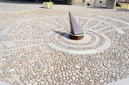reloj de sol: de metal reloj de sol en pavimento de piedra a las 9.55
