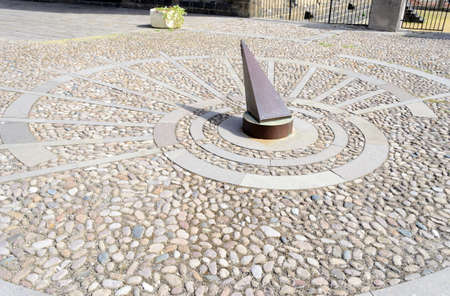 metal sundial on stone pavement at 9.55