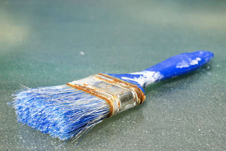 old blue paintbrush with rust on glass background Stock Photo