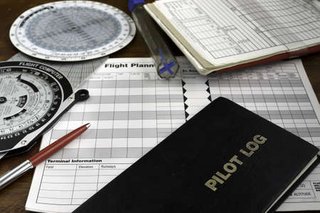 pilot log on a wooden table with headset, fuel tester and plotter