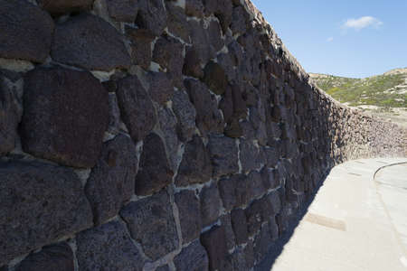 close up of a wall made of stones under a blue sky