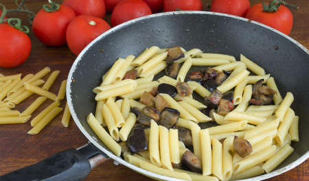 pan with pasta and eggplant on a wooden table