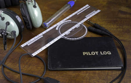 log book: pilot log on a wooden table with headset, fuel tester and plotter