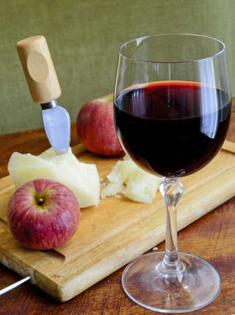 glass of red wine with cheese and apple on a chopping board photo
