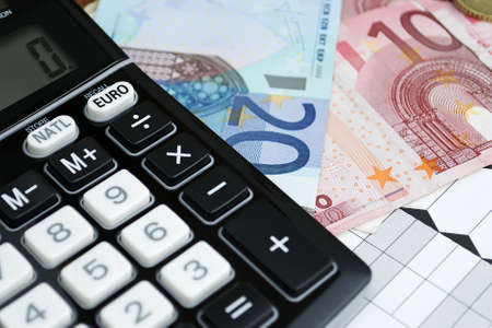 euro converter with euros bills and coins on a paper Foto de archivo
