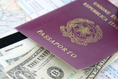 relocating: Italian passport, us dollars and airline ticket on a road map