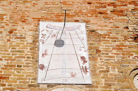 old sundial on a red bricks wall photo