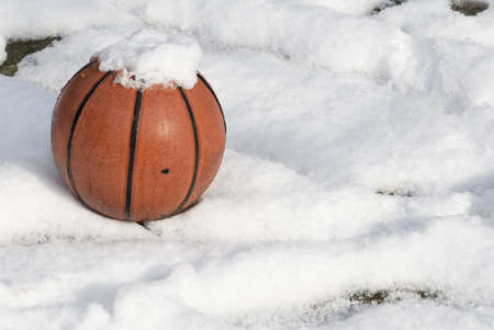 basketball on a playground covered by snow photo