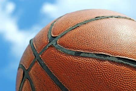 close up of a orange basketball under a blue sky