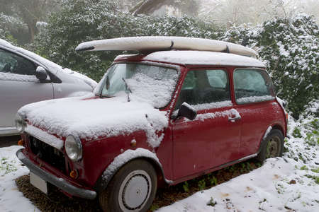 surfboard on a car roof covered by snow