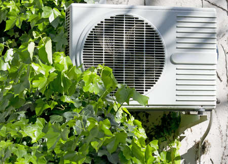 cold air: air conditioner surrouded by ivy