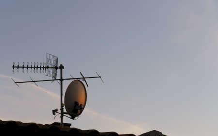 tv antenna and satellite dish at sunset photo