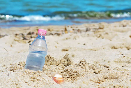 bottle with fresh water stuck in the sand photo