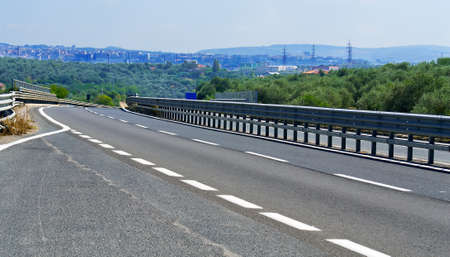 guardrail: detail of a road going to the city