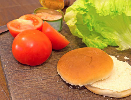 bun with knife, tomatoes and lettuce on a cutting board photo