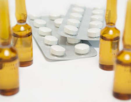 yellow phials and white pills on white background photo