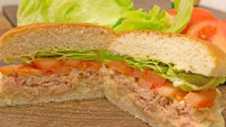 sandwich cut into halves on a wooden cutting board photo