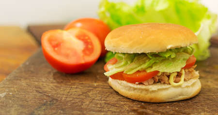 bun with tuna, tomatoes and lettuce on a cutting board photo