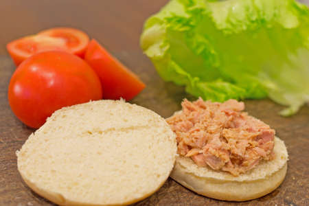 open bun with tuna on it and ingrendients all around photo