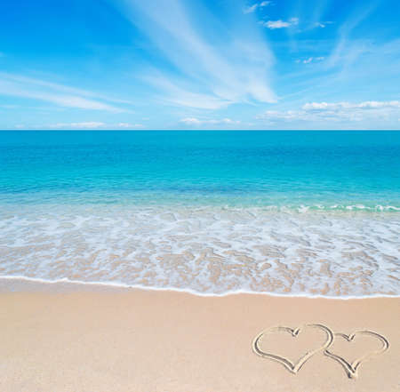 beach scene: turquoise water and golden sand in Sardinia with two hearts drawn in the sand on a cloudy day Stock Photo