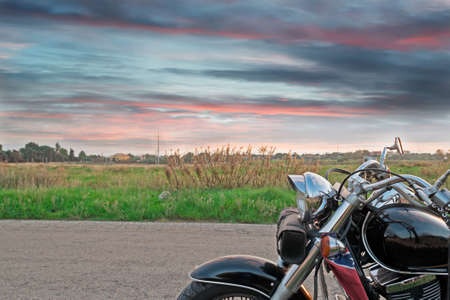 handlebar: chromed motorcycle on the edge of the road at sunset Stock Photo