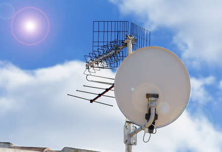 satellite dish under a bright sun Stock Photo
