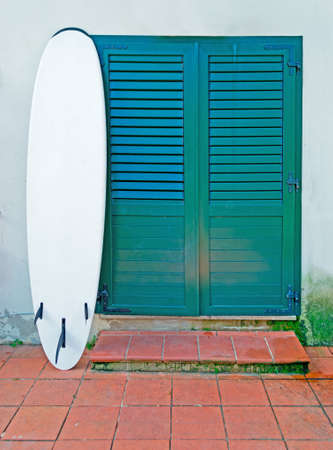 porch with entrance door and a white surfboard photo