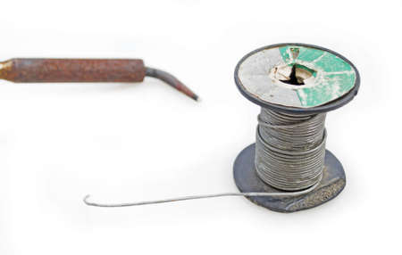 tin spool and soldering iron on white photo