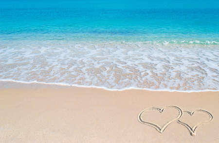 turquoise water and golden sand in Sardinia with two hearts drawn in the sand photo