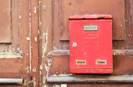 old red mailbox on a wooden door photo