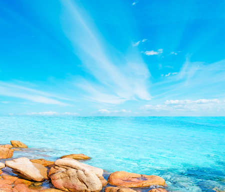 yellow rocks in turquoise sea under a blue sky